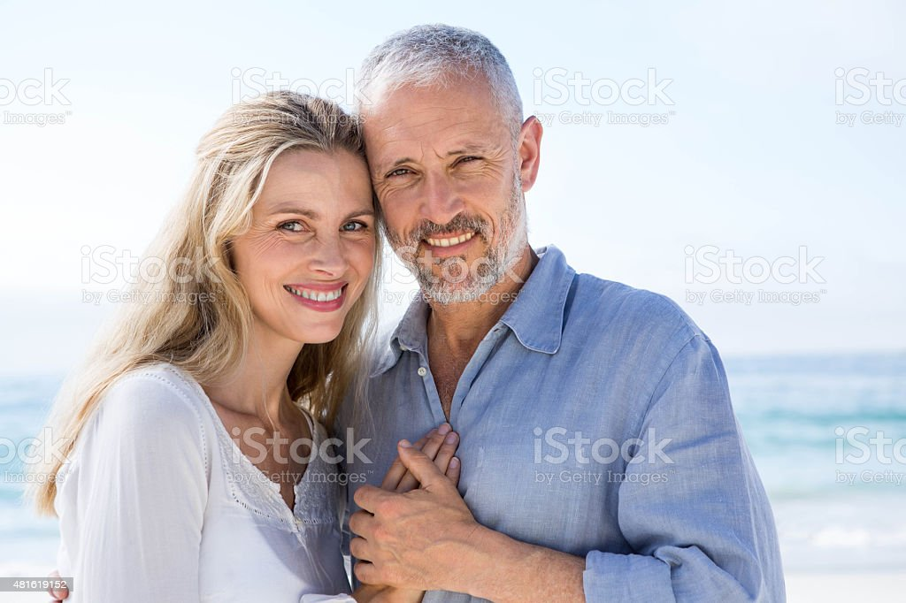 Happy couple hugging each other and looking at camera stock photo