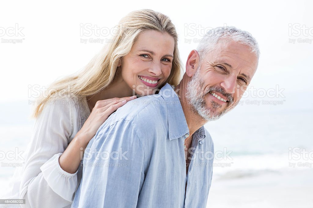 Happy couple hugging each other and smiling at camera stock photo