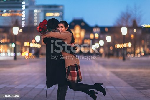 A happy Japanese couple is hugging each other in the street at night.