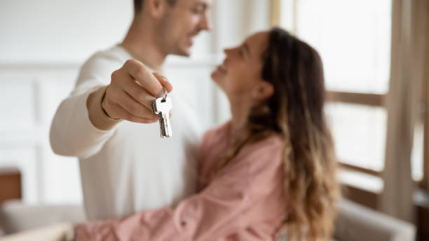 Happy couple hugging holding keys buy new apartment concept, closeup stock photo