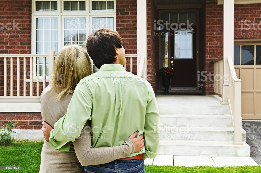 A happy couple hugging in front of a home stock photo
