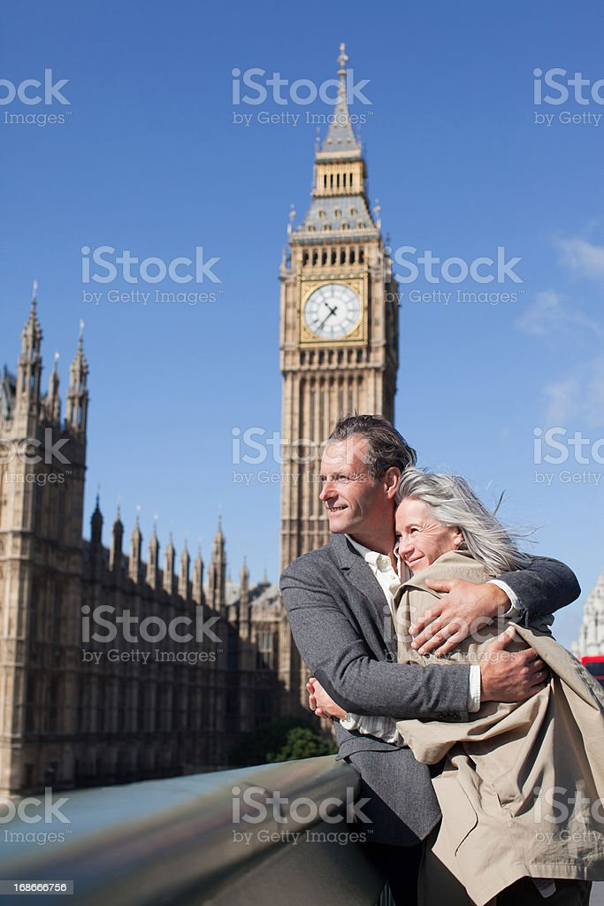 Happy couple hugging in front of Big Ben clocktower in London royalty-free stock photo