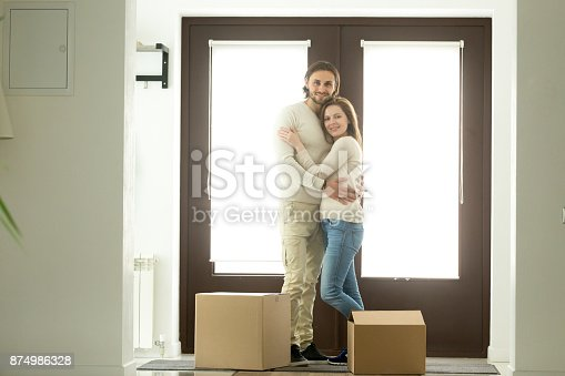938682826istockphoto Happy couple hugging looking at camera moving into new home 874986328