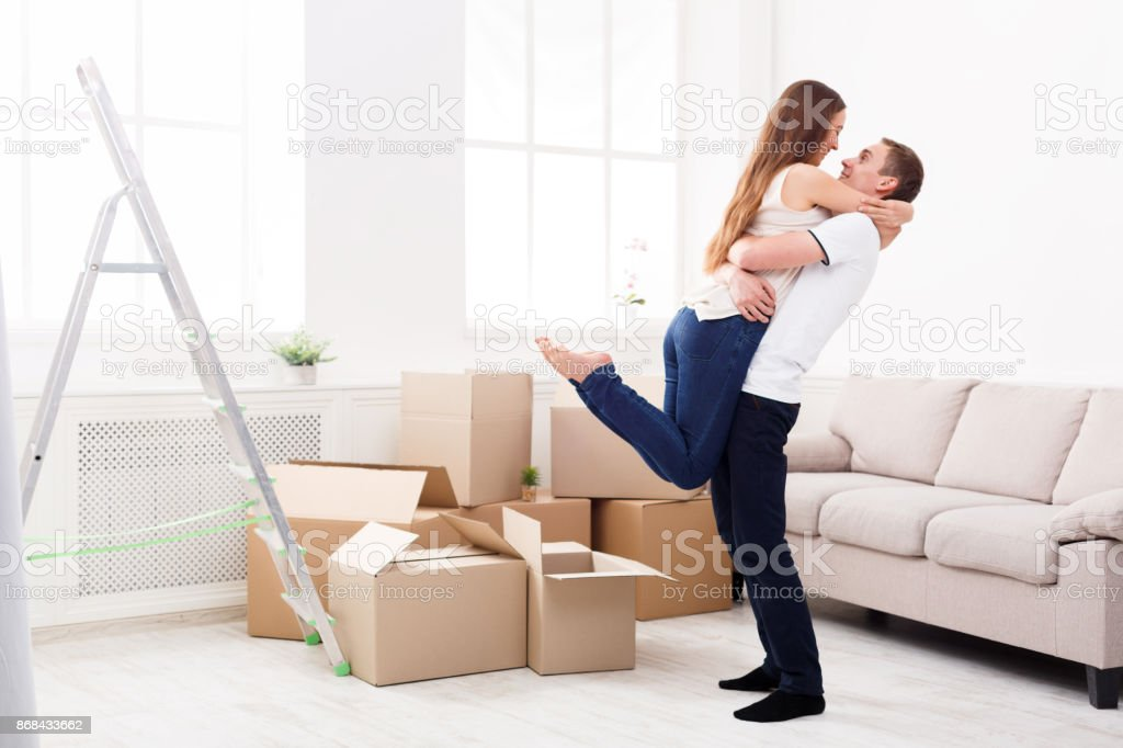 Happy couple hugging near unpacked boxes stock photo