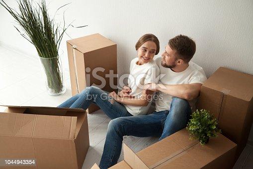 938682826istockphoto Happy couple hugging sitting on floor of own home 1044943354
