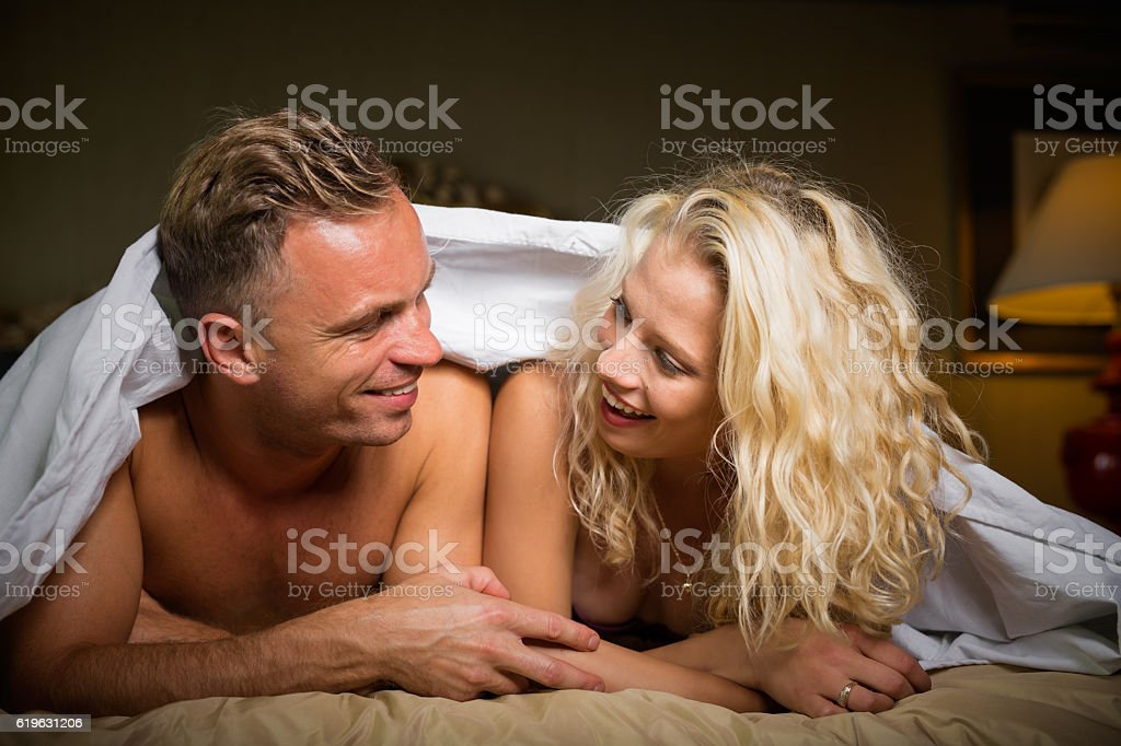 happy couple in bedroom looking at each other and smiling stock photo