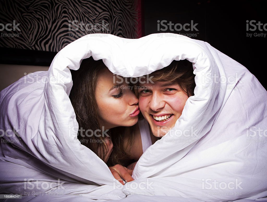Happy couple in heart shaped blanket royalty-free stock photo