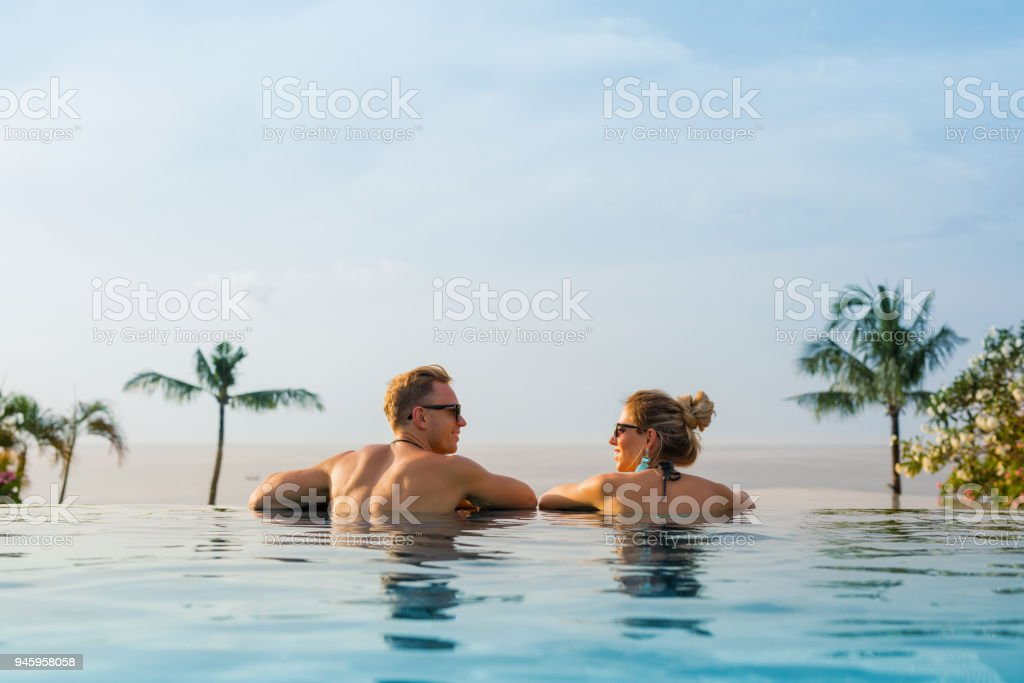 Happy couple in infinity pool stock photo