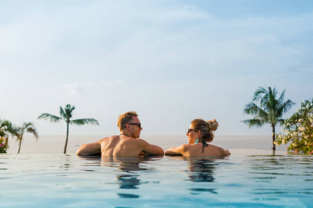 Happy couple in infinity pool Happy couple relaxing in infinity pool infinity pool stock pictures, royalty-free photos & images