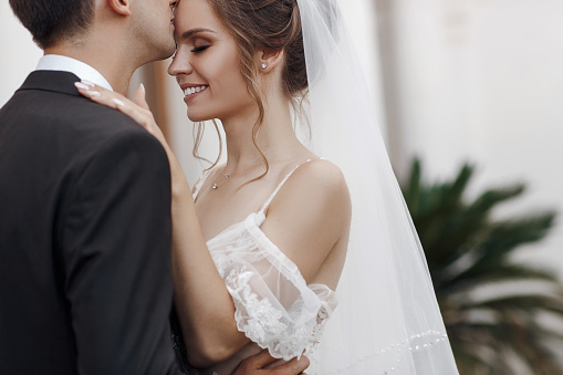 Bride and groom at wedding Day walking Outdoors on castle territory in summer. Bridal couple, Newlywed woman and man embracing with love. People happy and smile. The bride to the groom's hands. Happy couple in love look at each other