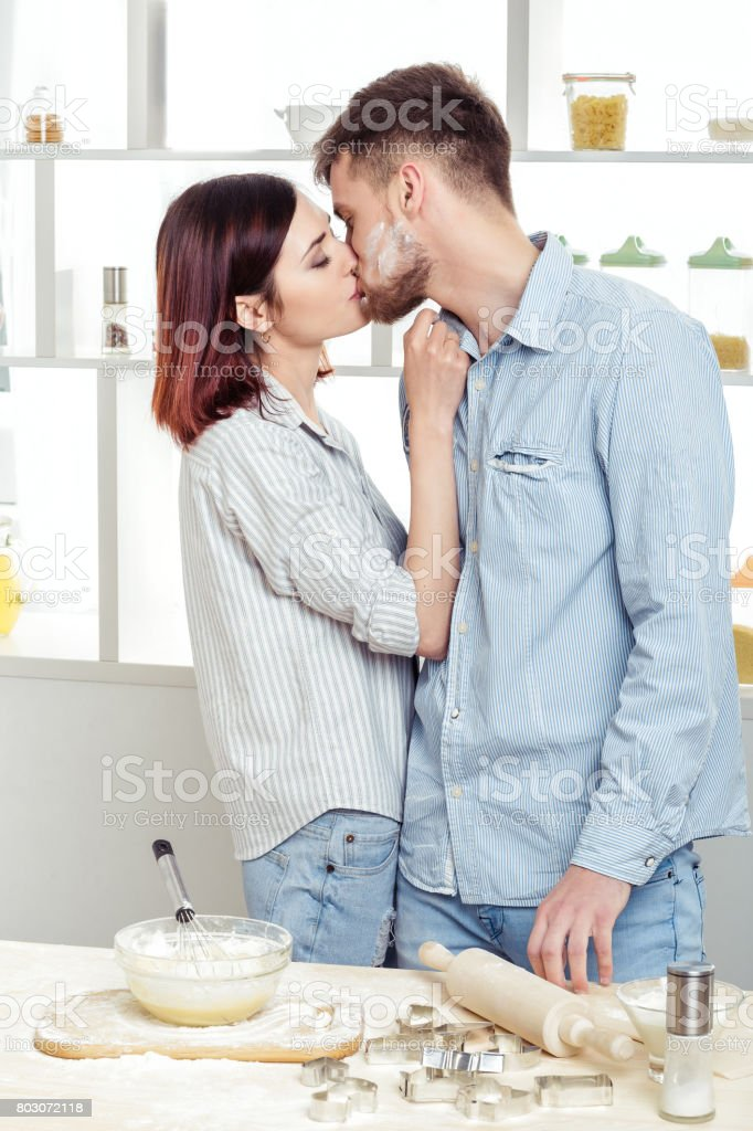 happy couple in love cooking dough and kissing in kitchen stock
