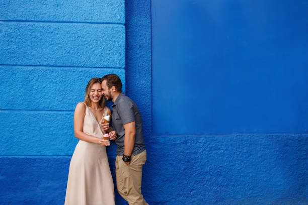 Happy couple in love eating ice cream and smiling against the blue wall stock photo