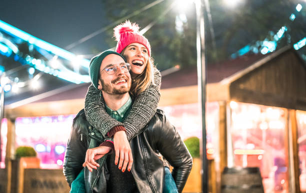Happy couple in love enjoying winter travel time outdoor - Handsome guy with nice girl on piggy back moment - Relationship concept with boyfriend and girlfriend together on warm vivid neon filter stock photo