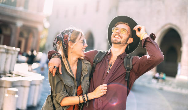 Happy couple in love having candid fun walking in city center - Wanderlust life style and travel vacation concept with guy and girl at old town tour on warm sunshine filter and backlighting stock photo