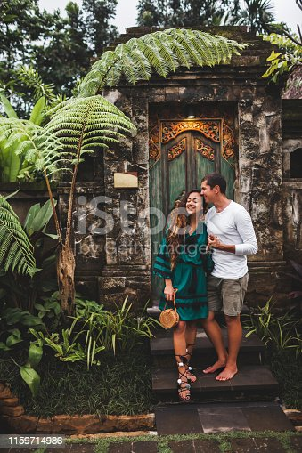 1065243116 istock photo Happy couple in love smiling and kissing on background of traditional balinese architecture 1159714986