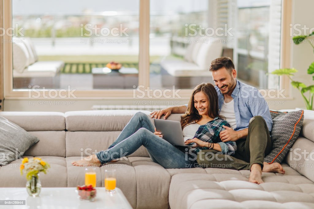 c14655a3cb Casal feliz no amor, navegar na Internet no laptop em casa. foto de stock