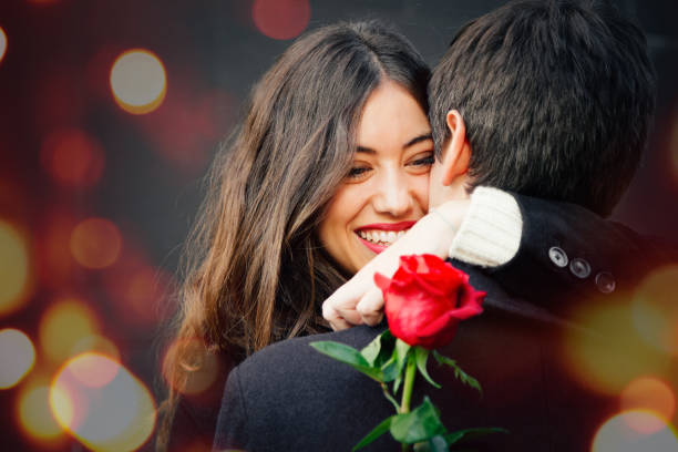 Happy couple in love with a rose embracing on the street stock photo