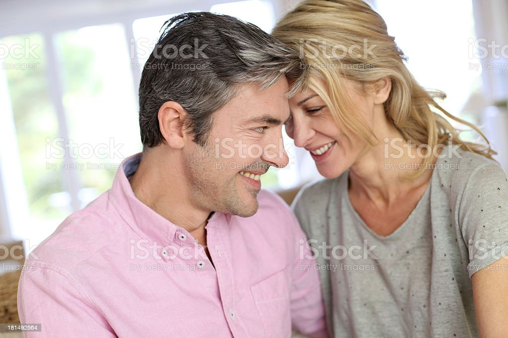 Happy couple in middle-aged sitting on sofa at home royalty-free stock photo