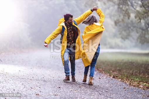 Young happy couple in raincoats having fun while dancing on rain in foggy forest. Copy space.