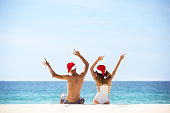 Happy couple in Santa's hats having fun and sits at tropical beach. New year beach holidays concept