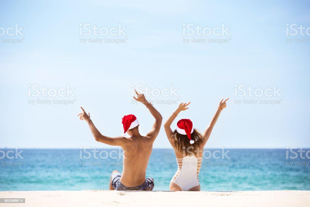 Pareja feliz con sombreros de Santa en playa tropical - foto de stock