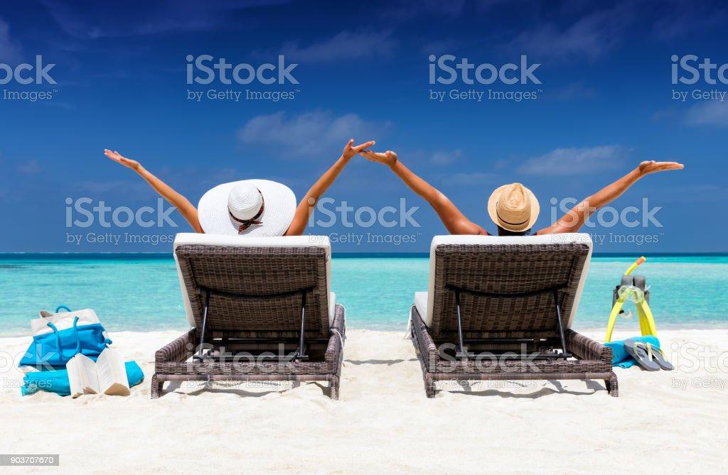 Casal feliz em espreguiçadeiras numa praia tropical - foto de acervo