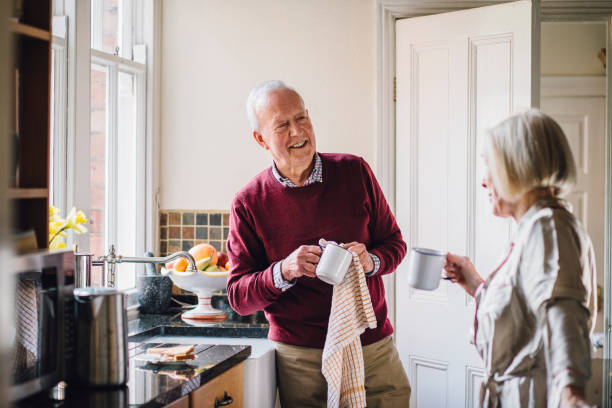 happy couple in the kitchen - senior housing stock photos and pictures