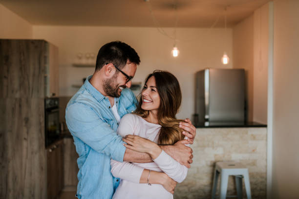 Happy couple in their new home. Young couple hugging indoors. stock photo