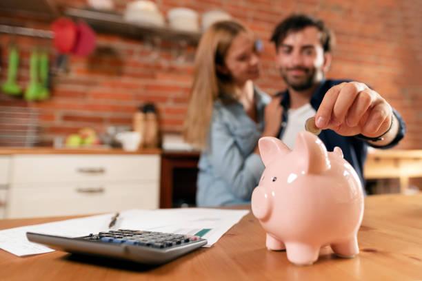 Happy couple inserting coin in piggybank – zdjęcie