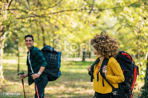 Couple hiking in forest.Young couple hiking together in mountains. Hiking - Hikers walking in the forest with poles on the path in the mountains, and hiking sticks poles. Man and woman hiking together.