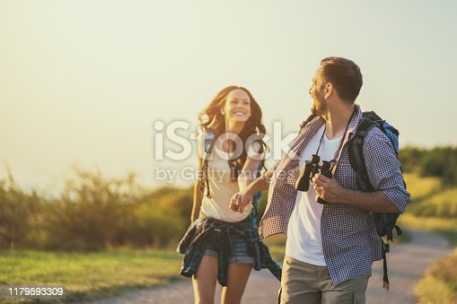 Young couple is running on country road in mountain.