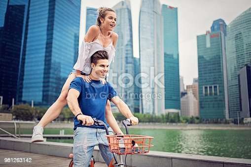 Happy couple is riding bicycle and make fun together