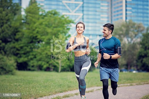 Happy couple is running in a city