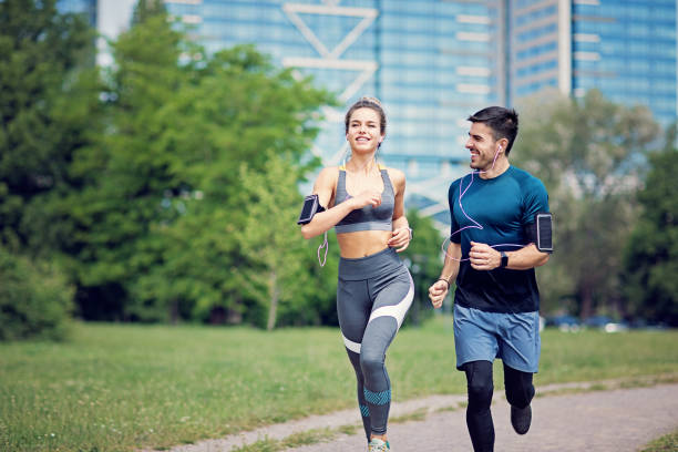 Happy couple is running in a city stock photo