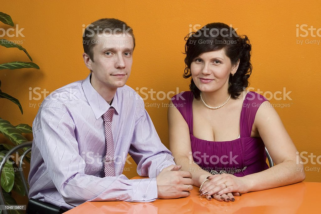 Happy couple is sitting at table in orange coffee house. stock photo