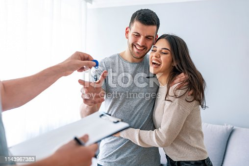 istock Happy couple is taking keys from their new house from broker and smiling. 1143967383