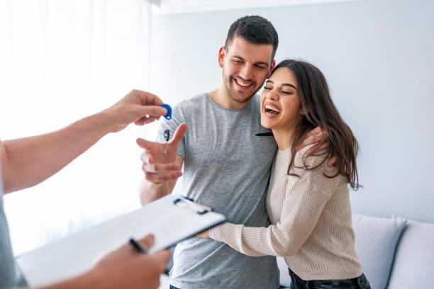 o par feliz está tomando chaves de sua casa nova do corretor e do sorriso. - chave - fotografias e filmes do acervo