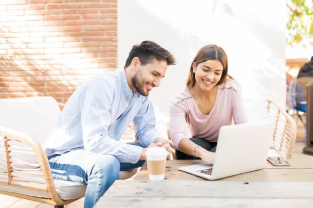 happy couple está usando el ordenador portátil en cafe - happy couple sharing a cup of coffee fotografías e imágenes de stock