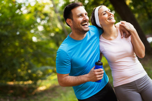 Happy couple jogging and running outdoors in nature stock photo
