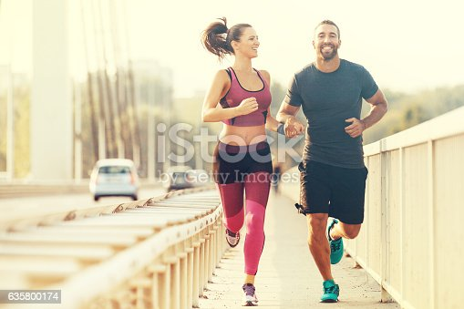 Early morning workout. Happy couple running accros the bridge. Living healthy lifestyle.