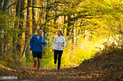 mature adult couple in their 40ies jogging through colorful indian summer autumn forrest in Austria during their workout