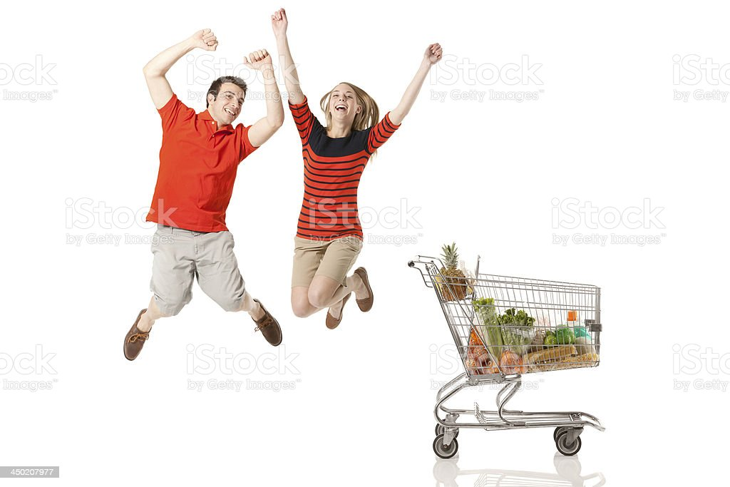 Happy couple jumping and shopping cart royalty-free stock photo