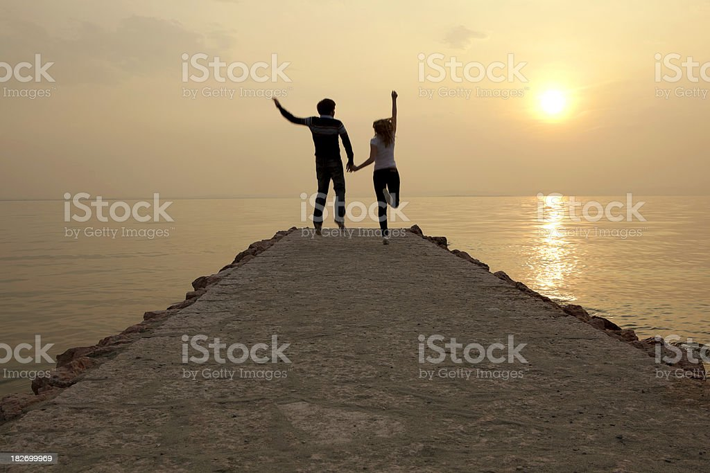 Happy couple jumping at sunset on a jetty royalty-free stock photo