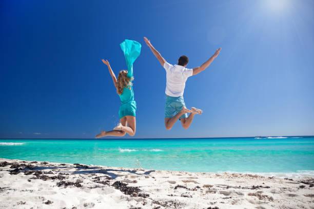 Happy couple jumping on beach stock photo