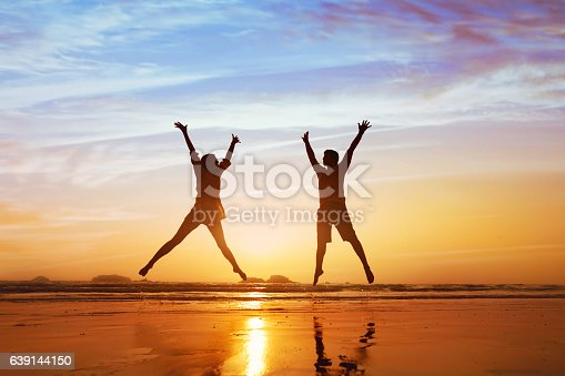 istock happy couple jumping on the beach at sunset 639144150