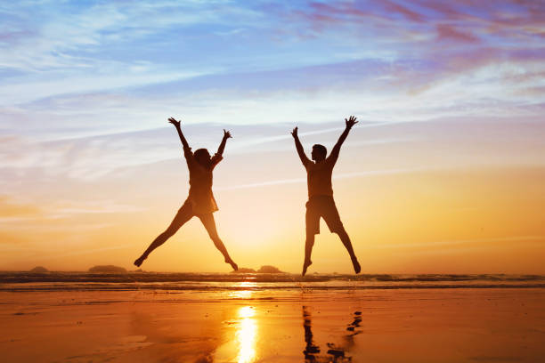 happy couple jumping on the beach at sunset - foto stock