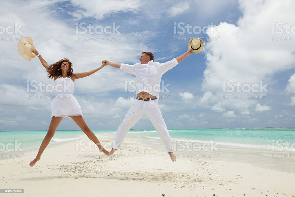 Happy couple jumping on the tropical beach stock photo