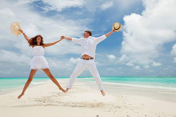 Glückliches Paar springen am tropischen Strand – Foto