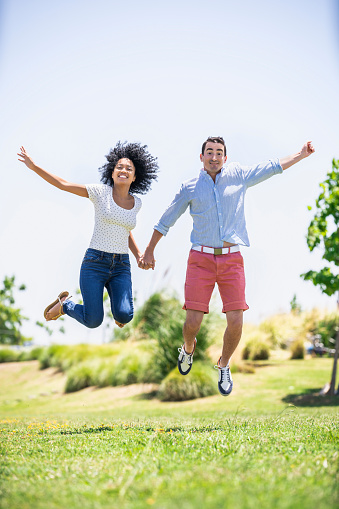 Happy couple jumping together in garden