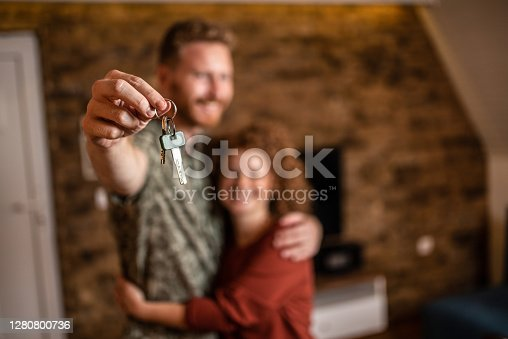 Happy young couple holding a key of their new home in front of camera.